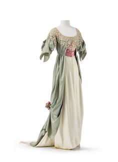 Evening dress by Jeanne Paquin, spring/summer collection, Paris, 1912. This dress in pastel shades combines a tunique in light green silk in tabby weave with a skirt made of cream silk satin. The rose red corset belt accentuates the high waist.