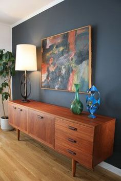 Darker reddish brown Teak credenza against a darker blue /grey accent wall. Light accent colors blue / green.