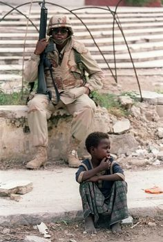 An armed US soldier and a young Somalian boy sit in a street, 6 January 1993 in Mogadishu capital of Somalia, during 'Restore Hope' operation. Since 3 December 1992, the UN authorised US troops to deploy in Somalia in order to restore peace after civil anarchy caused by roving gangs gunmen attached to local warlords.