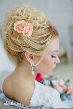 curly top knot updo hairstyle with coral roses