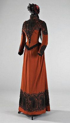 John Redfern three-piece walking suit, circa 1889, of brown felted wool with black soutache braid and astrakhan trim, comprising: fitted boned bodice with side buttoning; skirt with fullness at the back; matching bonnet by Louise & Co. of Regent Street.