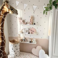 Half painted nursery wall in pink and polka dot wallpaper
