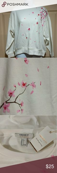 blossom embroidered oversized sweat shirt. This oversized sweatshirt is really beautiful. The embroidered cherry blossoms are vibrant and scattered about the front of the shirt and wrapped around a little bit onto the back. It says it's a size small, but I'm a size 8-10 and it it's me, and is still oversized. This is not a bad thing, it is well proportioned and as it is supposed to be. Super comfy and soft on the inside. Never worn, tags attached. Forever 21 Tops Sweatshirts & Hoodies
