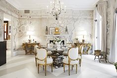 The formal dining room designed by Alex Papachristidis spills over with ornate detail, depicting a faux classic scene with muted trompe l'oeil wall-coverings. Explore the full home tour.