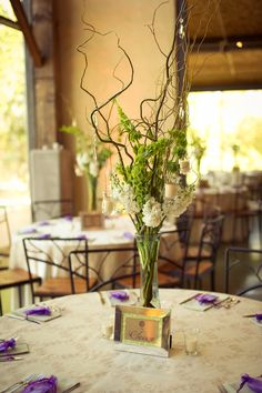 The other tables will feature a tall hourglass vase filled with brown curly willow with a band of green hydrangeas, coral spray roses, white lisianthus, and green hypericum berries and hanging candles.