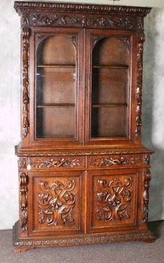 """18th C heavily carved Black Forest 2 part cabinet with 2 glass doors above 2 drawers over 2 doors. H:91. 5"""" W:52. 75"""" D:21"""""""