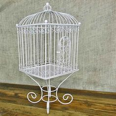 A white wire bird cage that can be used as a wedding card holder or can be paired with candles, plants or other decor items. Removable base allows you to use the bird cage as a cloche for even more decorating possibilities.