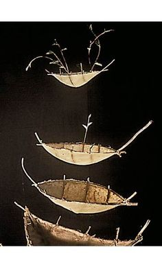 """Nesting Boats by Catherine Nash Cast HMPaper of varied fibers: cedar bark, torch ginger grass,gampi and kozo fibers, branches, straw. Top two boats """"sprout"""" green gampi paper leaves. 6.5 X 2 X 4 ft."""