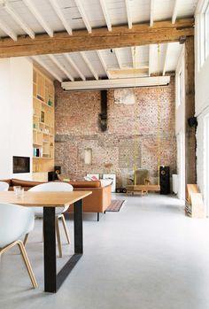 Un séjour new-yorkais avec balançoire, poutres et briques apparentes.