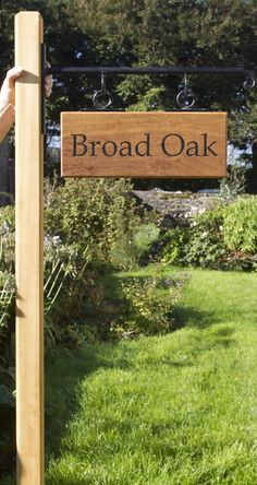 An iroko wood sign hanging from iroko post with wrought iron scroll bracket - ref - 1309.LW.068 www.sign-maker.net/wooden/iroko.htm