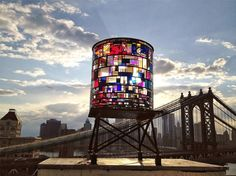 "the ""monumental sculpture, Watertower, is built out of salvaged plexiglass and steel, and is mounted high upon a water tower platform located in DUMBO, Brooklyn. The mosaic design consists of about 1,000 scraps of plexiglass that were retrieved from all over New York City, ranging from old sign shops to closed-down artist studios and various warehouses."""