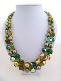 60s glass necklace with a variety of green and gold toned beads and AB finishes