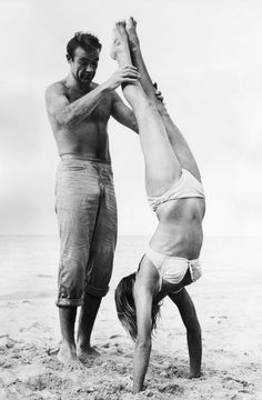Sean Connery and Ursula Andress playing on the beach during the filming of Dr. No, 1962