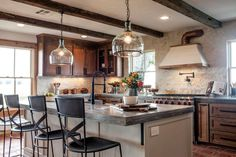 The drop ceiling was removed and exposed wood beams added for a coffered effect. New stainless appliances were added as well as all new lighting and special features such as a wall-mounted pot-filling faucet and a custom vent hood with copper accents.