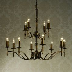 Elegant 12 arm chandelier in an antique brass finish.  Handmade in England to the highest quality.