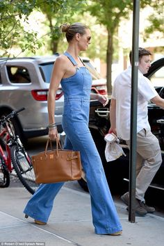 No need: The dungarees' fit ensured the star could skip wearing a top underneath showing off her shoulders and decolletage, making the look sexier