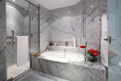 White marble bathroom offers a possibility to choose between relaxing tub or quick shower