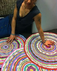 Mandra, femme rom de Montreuil et auto-entrepreneuse, accompagnée par les Filles du Facteur, pose devant ses oeuvres, de magnifiques tapis multicolores crochetés