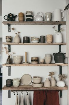 a collection of wabi sabi handmade ceramics on raw edged shelving create a simple but beautiful modern rustic kitchen look