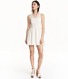 Short, sleeveless dress with a lace bodice. Concealed zip at back and gently flared skirt in woven crêpe fabric. Lined.
