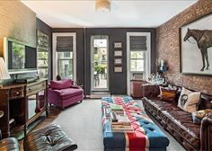 Greenwich Village living room- love the Union Jack tufted ottoman and leather chesterfield against the exposed brick wall.