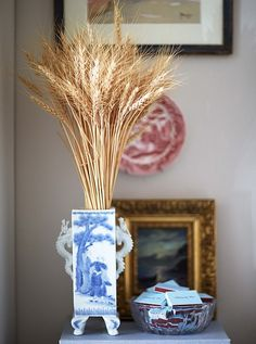 Wheat brings a natural note to a chinoiserie vase and balances the more ornate gilt frame andintricately paintedplate.