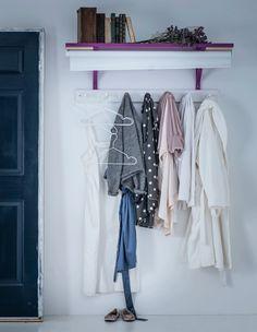 Kleidung an einer Wand aufgehängt und verborgen hinter einem selbst bemalten TUPPLUR Verdunklungsrollo in Weiß