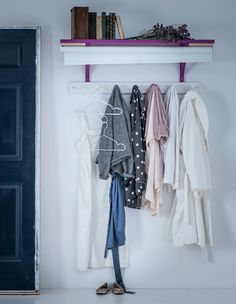 Clothing is hung on wall hooks underneath a shelf and hidden away by a hand-painted TUPPLUR blackout blind.