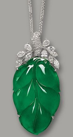 JADEITE 'LEAF' AND DIAMOND PENDANT NECKLACE The highly translucent jadeite of emerald green colour, carved as a 'leaf', embellished by marquise- and pear-shaped diamonds together weighing approximately 2.70 carats, accompanied by a link-chain, mounted in 18 karat white gold, length approximately 450mm. Leaf approximately 49.66 x 30.65 x 4.35mm.