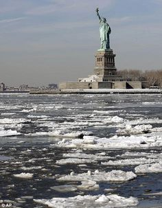 Ice flows past the Statue of Liberty, Tuesday, Feb. 24, 2015, in New York. A wide swath of...