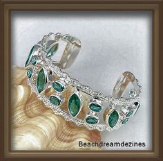 Beautiful Turquoise ocean green crystals are bezel set into silver color bangle There are 6 Marquis shaped crystals and 14 oval shaped