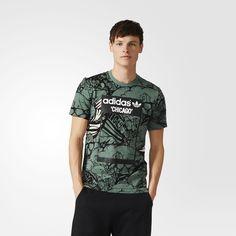 """Uma parceria entre a adidas Originals e JC Rivera, esta camiseta masculina exibe a marca registrada do artista americano, ursos, espalhados pelas ruas de Chicago, sua cidade natal. A etiqueta na parte de trás finaliza a peça com seu apelido, """"The Bear Champ""""."""