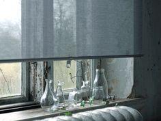 Nærbilde av ei grå rullegardin som skjermer for lys, vist i et vindu.