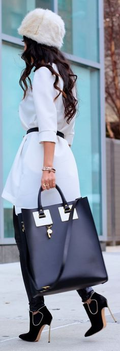 Gorgeous Fall/Winter Style Collection. Business lady wearing white coat, plushy hat and high-heeled shoes