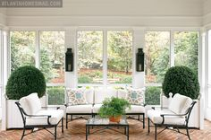 """A vaulted ceiling helps create an airy feel, while floor-to-ceiling screens blur the boundaries between indoors and out. Another highlight of this spacious room is the pair of American boxwoods in custom planters. """"It's very peaceful to sit out here with my dogs, although there's been some collateral damage with them punching through the screens when they were puppies,"""" Elsey jokes."""