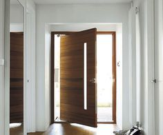 Hallway with oversized door. Consider Phantom Screens and start improving indoor air quality, enhancing home functionality and reducing cooling costs. House Design, New Homes, Windows And Doors, House Front Door, Cool Doors, Home, House Doors, Pivot Doors, Exterior Doors