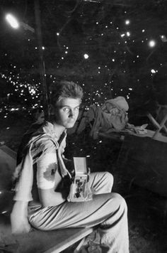 Private Robert Scullion holding Purple Heart he was awarded after being wounded by shellfire while in the hospital (note shrapnel holes in tent wall)