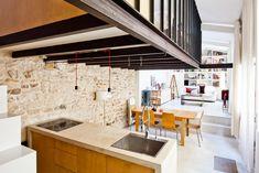 Solida e compatta, la cucina è realizzata in cemento e ciliegio ed è sormontata dal soppalco in acciaio e vetro