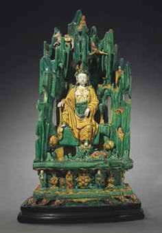 A LARGE GREEN, YELLOW AND CREAM-GLAZED STONEWARE FIGURE OF THE 'WATER-MOON' GUANYIN IN A GROTTO
