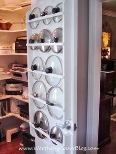 A diy pot lid holder on a door in the kitchen