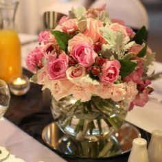 Various pink blooms in fish bowl glass vases