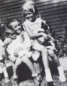 Norma Jeane (Marilyn Monroe) holding Tippy, with her foster brother, Lester Bolender, and another child, ca.1933.