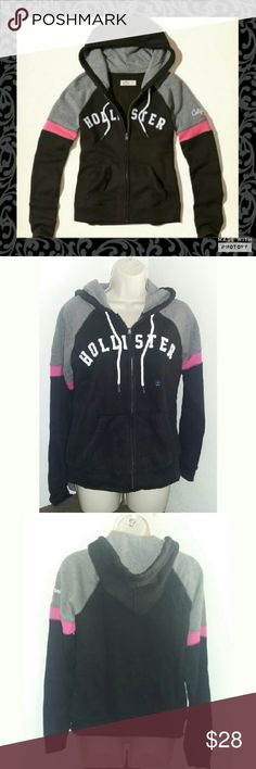 Hollister Zip up Sweater Sweater is black with white, pink, and gray design. Size large. New with tags. Warm comfortable material. Has Hollister across chest and California written on sleeve. 60% cotton 40% polyester material. Hollister Tops Sweatshirts & Hoodies