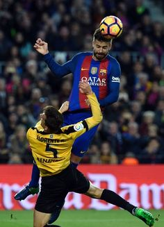 Barcelona's defender Gerard Pique (R) heads the ball past Malaga's midfielder Mikel during the Spanish league football match FC Barcelona vs Malaga CF at the Camp Nou stadium in Barcelona, on November 19, 2016. / AFP / LLUIS GENE