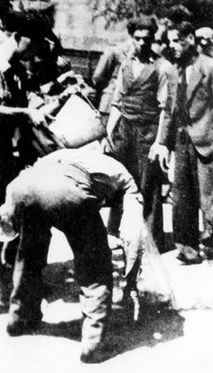 """Saloniki, Greece, """"Black Sabbath"""", 11/07/1942. On """"Black Sabbath"""", 9000 Jewish men of ages 18-45 were forced to gather in the """"Freedom square"""" where they were humiliated for the entire day. In this photograph a soldier is pouring water on a Jew's head."""