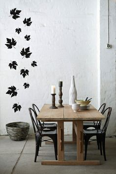 Wow...stenciled leaves on the wall, and it matches the black chairs.  Great contrast and creativity.