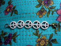 """Pulseira com pingentes do símbolo """"Paz e Amor"""" em resina creme. R$42,90"""