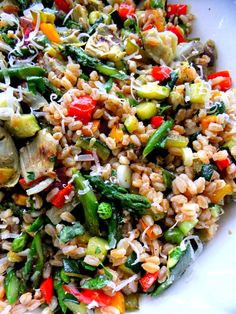 A Big Serving Bowl Of Springtime Farro Salad with Roasted Bell Peppers, Asparagus, Garlic, Zucchini, Artichoke Hearts, and Peas...