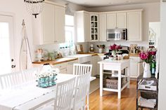 I love this kitchen. I plan to do white cabinets when we re-do our kitchen. I had planned on a vellum yellow color for the walls, but I think I like the light grey look here. seen on French Larkspur.