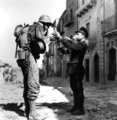 An Italian civilian policeman provides an American soldier a refreshing drink of water following Operation Husky: the Allied invasion of Sicily and the capture of the town of Troina from Axis forces. The town was mostly destroyed during six days of fighting. Troina, Province of Enna, Sicily, Italy. August 1943.